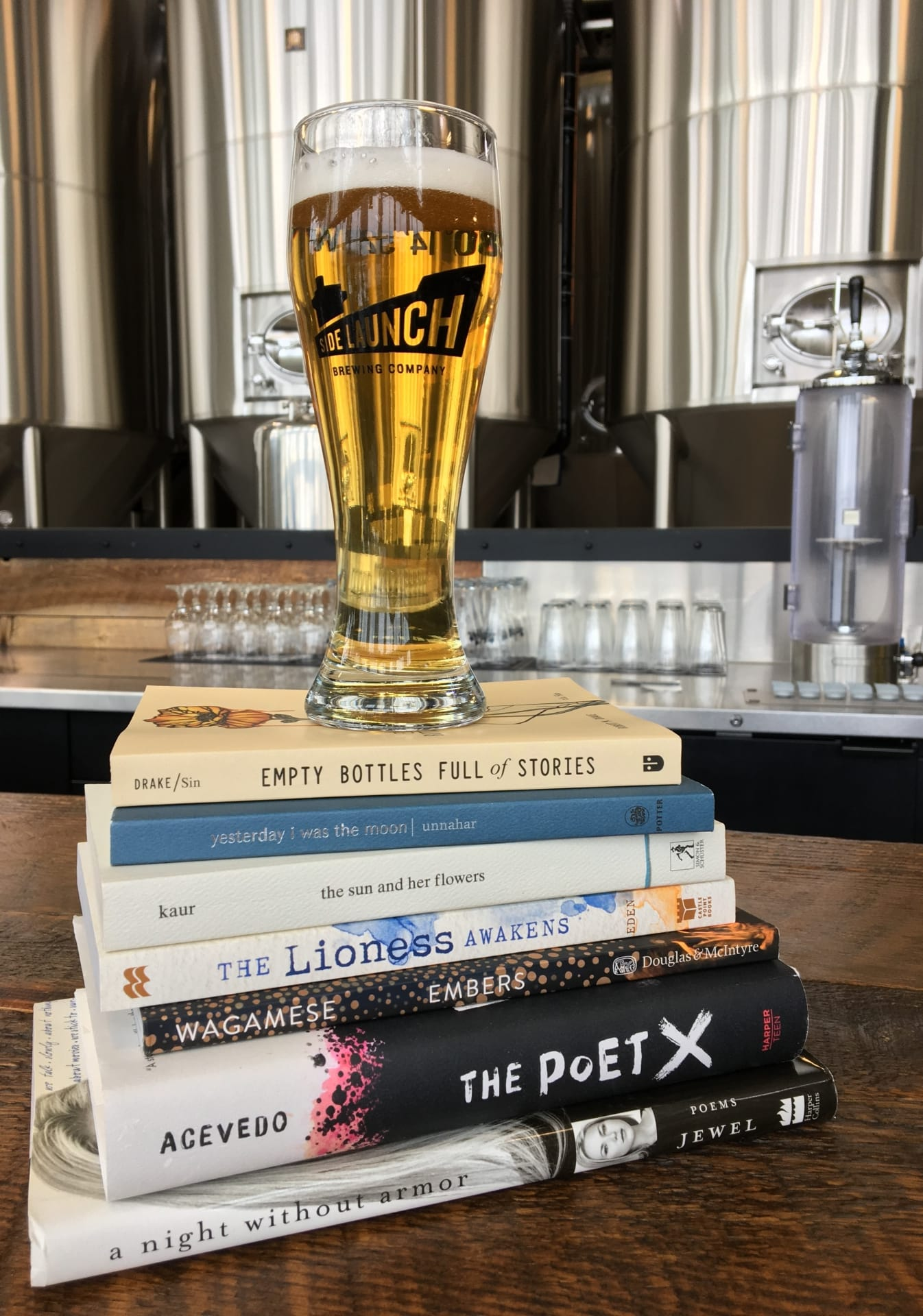 Glass of Side Launch beer on top of stacked poetry books