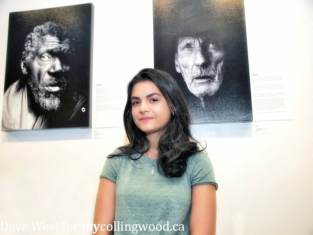 Leah Denbok with her photos on the wall behind her