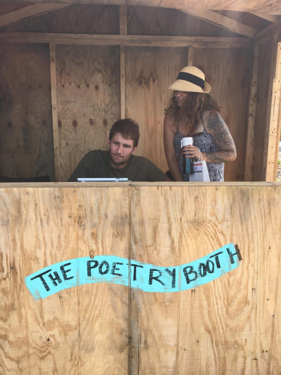 A couple having fun writing in the poetry booth
