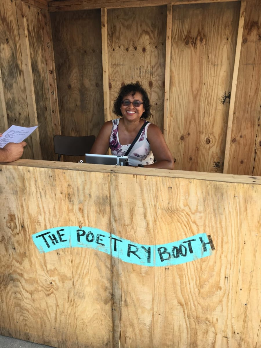 A woman smiles from inside the wooden poetry booth at Sidelaunch Days harbour festival this August