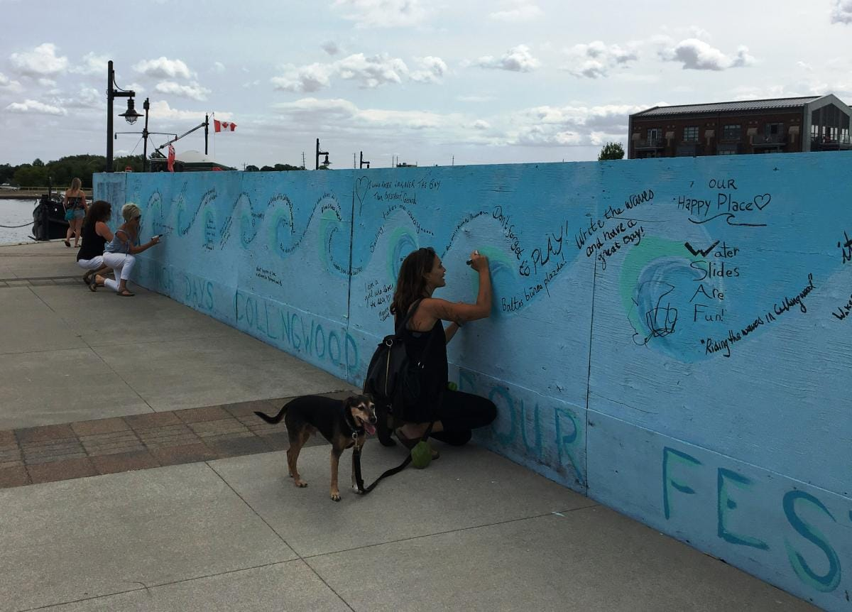 A woman and her dog pause at the wall